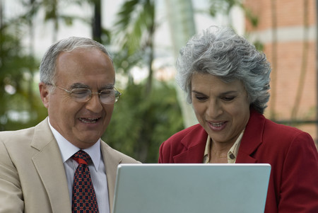 saturating: Senior Hispanic couple looking at laptop LANG_EVOIMAGES