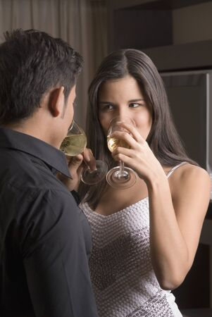 conferring: Hispanic couple drinking wine LANG_EVOIMAGES