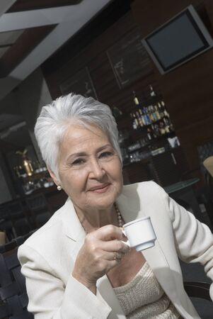 Senior Hispanic woman drinking coffee