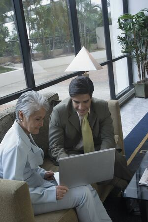 conferring: Hispanic businesspeople looking at laptop