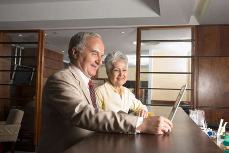 two persons only: Senior Hispanic businesspeople looking at laptop LANG_EVOIMAGES
