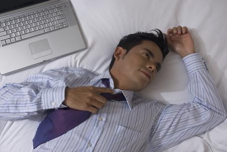 portable failure: Hispanic businessman laying on bed