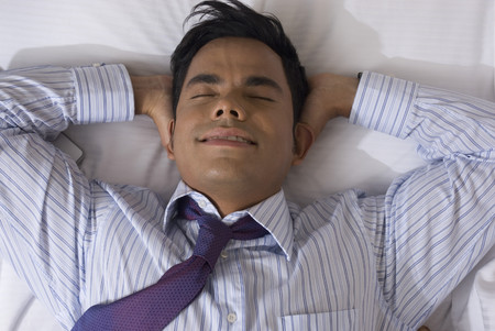 wearying: Hispanic businessman laying on bed