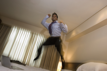 tipping: Hispanic businessman jumping on bed
