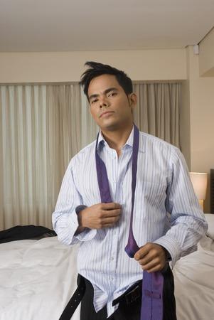 eyes downcast: Hispanic businessman getting dressed