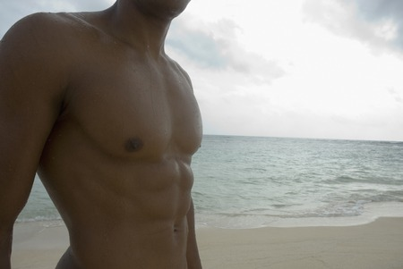 barechested: Bare-chested Hispanic man at beach