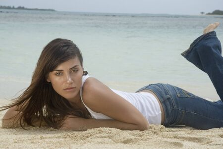 low spirited: Woman laying on beach LANG_EVOIMAGES