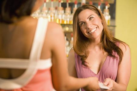 attired: Hispanic female sales clerk taking credit card