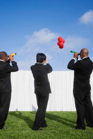 searcher: Multi-ethnic businessmen looking over fence at balloons