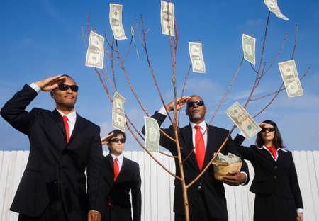 cutting costs: Multi-ethnic businesspeople saluting money tree LANG_EVOIMAGES