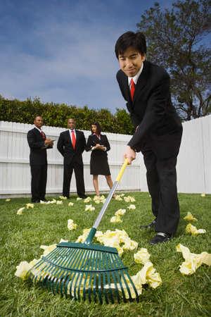 corporate espionage: Asian businessman raking up crumpled paper
