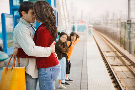 coming together: Hispanic couple hugging at train station