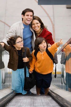 conferring: Hispanic family on escalator LANG_EVOIMAGES