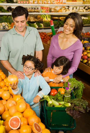 Hispanic family shopping in grocery store Stock Photo
