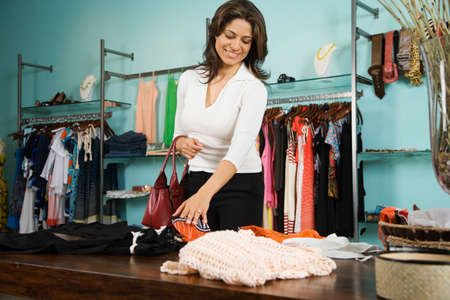 fortitude: Hispanic woman shopping in clothing store