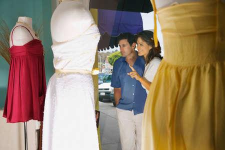 low blouse: Hispanic couple window shopping