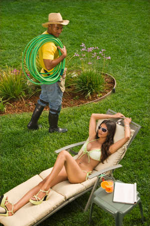 dollarbill: Gardener looking at Hispanic woman sunbathing