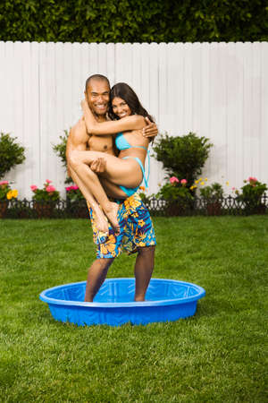 stepping: Multi-ethnic couple standing in kiddie pool