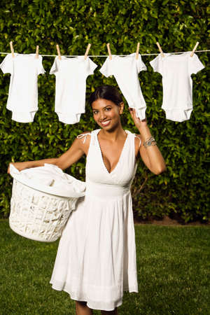 harmonizing: Hispanic woman hanging baby clothing on clothes line LANG_EVOIMAGES