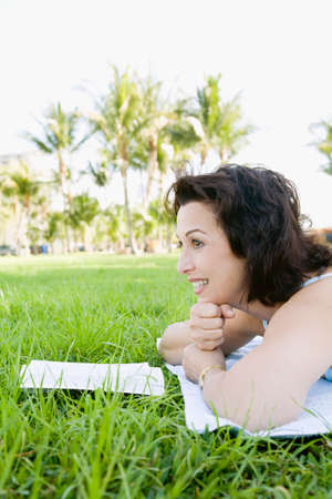 scowling: Hispanic woman reading in grass
