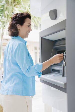 automatic teller machine: Mujer hisp�nica que usa cajero autom�tico