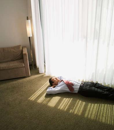 Asian businessman laying on hotel room floor