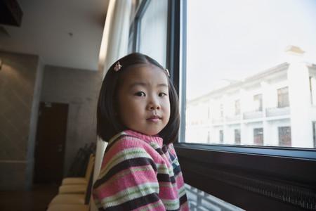 Asian girl next to window Imagens