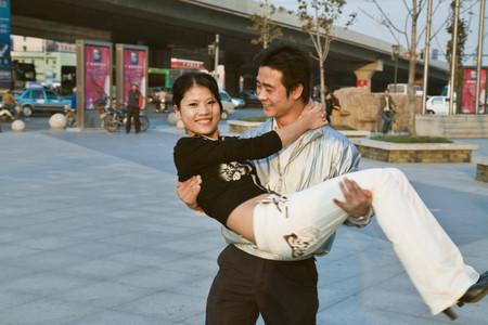carrying girlfriend: Asian man carrying girlfriend