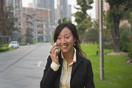 conferring: Asian businesswoman talking on cell phone