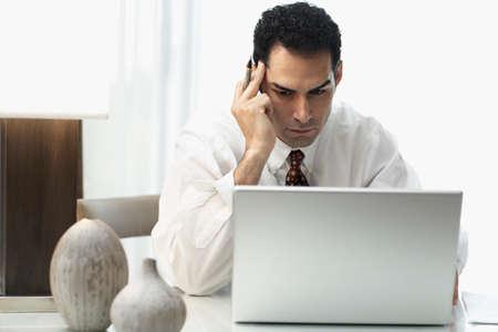 motioning: Hispanic businessman looking at laptop LANG_EVOIMAGES