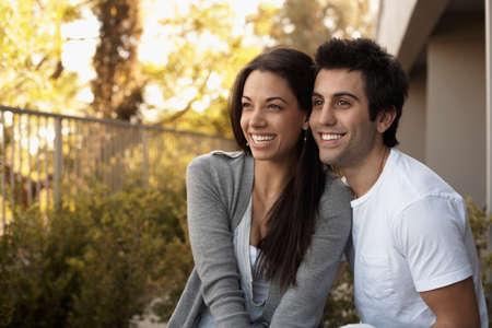 attired: Multi-ethnic couple hugging