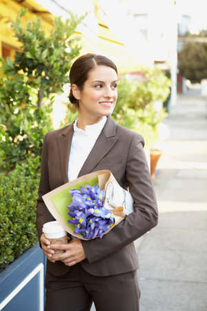 well beings: Hispanic businesswoman carrying flowers