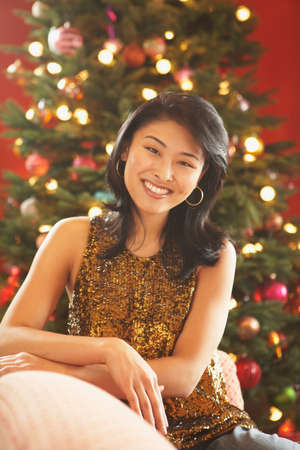 gratifying: Asian woman in front of Christmas tree