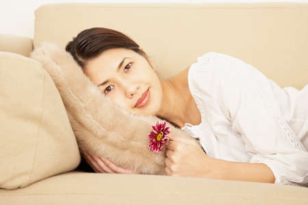 light hearted: Asian woman laying on sofa