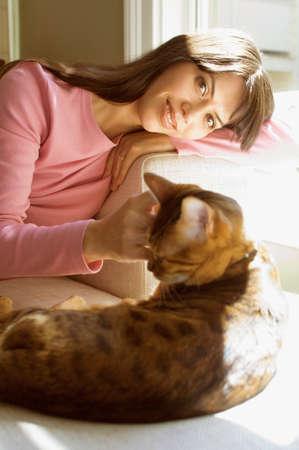 liveliness: Hispanic woman petting cat LANG_EVOIMAGES