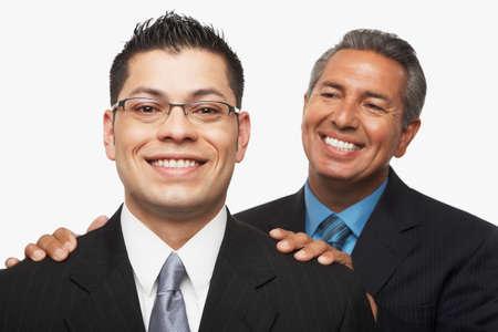 younger: Hispanic businessman smiling at younger businessman LANG_EVOIMAGES
