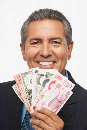 possessive: Hispanic businessman holding assorted world currencies