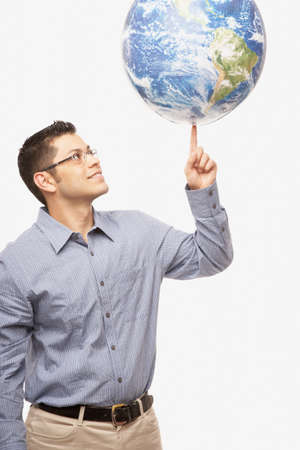fingertip: Hispanic man balancing globe on fingertip