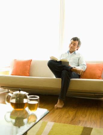 sofa: Hispanic man reading on sofa