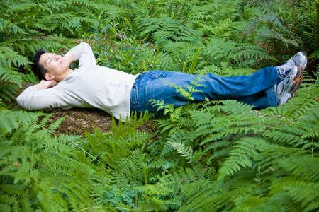 nite: Asian man laying in woods
