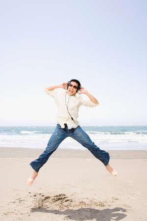 spectating: Asian man jumping on beach