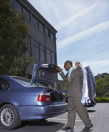 dry cleaning: African businessman holding dry cleaning