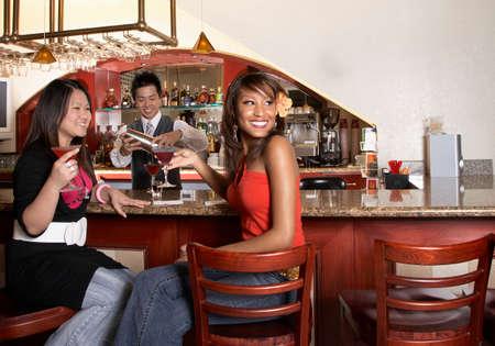 Multi-ethnic women sitting at bar