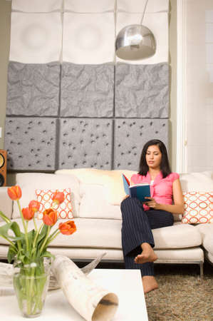 Indian woman reading on sofa Stock Photo