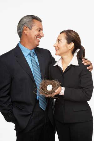 joining forces: Hispanic professional couple holding nest with dollar sign egg
