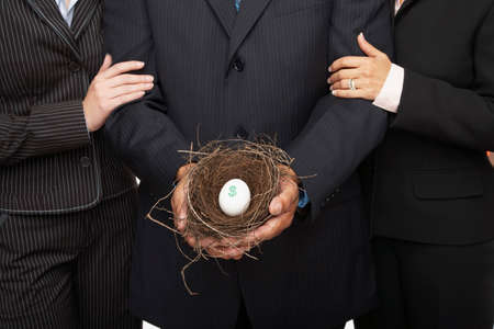 interrogating: Hispanic businesspeople holding nest with dollar sign egg