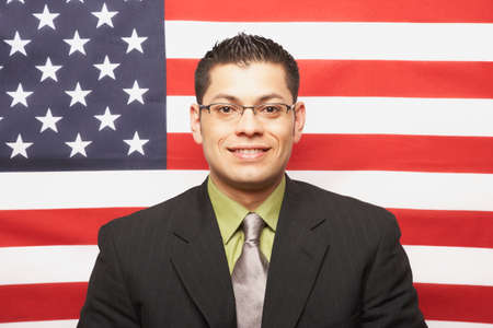 prevailing: Hispanic businessman in front of American flag