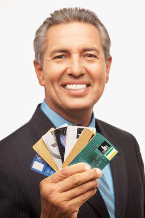 tact: Hispanic businessman holding credit cards LANG_EVOIMAGES