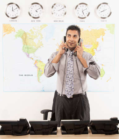smooching: Indian businessman talking on two telephones