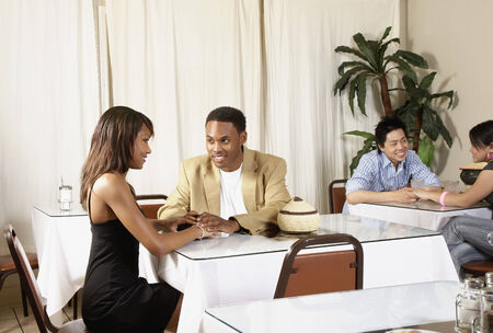 barkeep: African American couple holding hands at table
